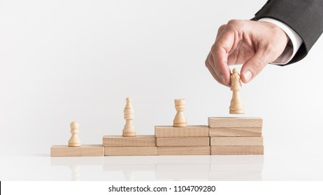 Four chess pieces on a stepped stack of wooden blocks with a businessman placing a queen piece on the highest level conceptual of success and winning.