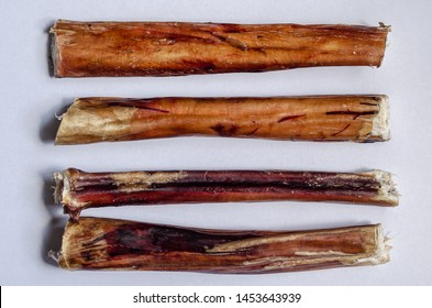 Four chew bully sticks. Dried beef pizzle for pets. Horizontal layout option. White background. Shooting from above. Macro. Natural dried treats for dogs. Favorite bully sticks puppies and pets.