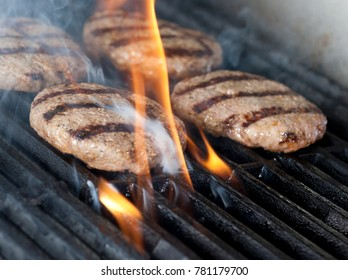 Four Chicken meat burger steaks on the grill with flames. cooking chicken grilling or bbq or barbecue on charcoals. Close up