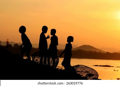 Four children, girls and boys walk along the Mekong River at sunset