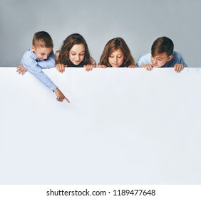 a Four children holding a big billboard, looking down on it.