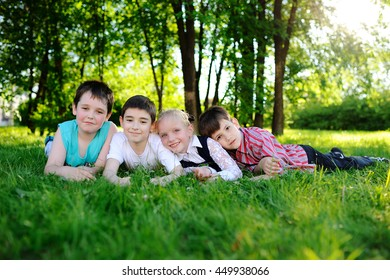 four children lie on their stomachs on the grass and smiling. Childhood, friendship, summer, vacation, camp.