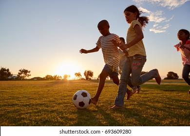 Four children racing after a football plying on a field