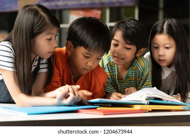Four children siit and reading book at school,fun and happy,education concept,learning and knowlage.