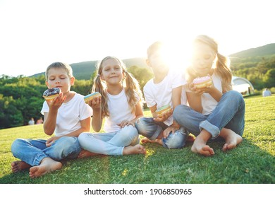 Four children sit on green grass on the ground and eat donuts and smile, sweet food, good friendship, love and happiness without borders . High quality photo.