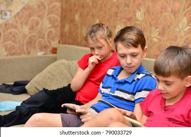 Four children, slouching on a couch in a living room, gaming on tablets and smart phones, being bored