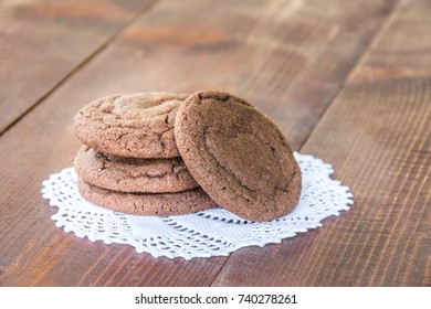 Four chocolate cookies on white handmade doily on dark brown wooden table