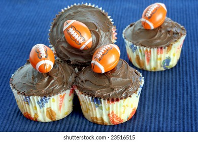 Four chocolate cupcakes with football decorations perfect for football or Father's Day treats