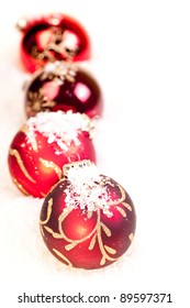 Four Christmas red baubles on snow as a white background
