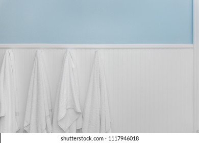 Four clean white towels hang from hooks on white beadboard or wainscoting with light blue wall paint
