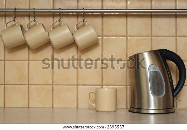 Four coffee cups hanging in a row. Single cup and electric cordless kettle sitting on table