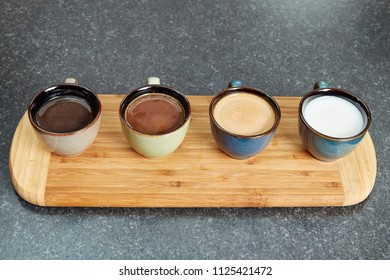 Four coffee cups in a row on a wooden bar displaying different mixtures of milk and coffee