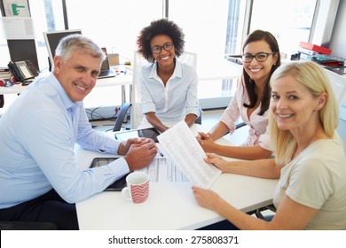 Four colleagues meeting around a table in an office