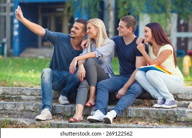 Four college students taking selfie with a smart phone