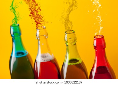 Four color bottles with young wine on yellow background