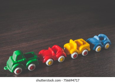Four color cars model on wooden background with copy space. concept of car rental, auto car insurance and traveling