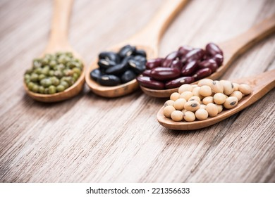 four colored beans in wooden spoon.selective focus is soybeans