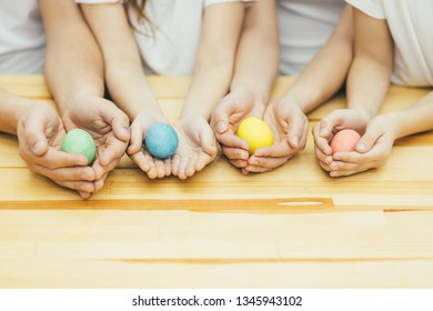 Four colored easter eggs in mother father sister and brother's hands like in the nests. Blurred background.