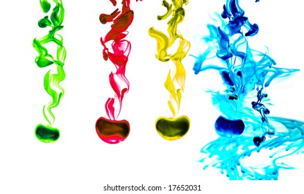Four colored ink drops flowing in water with a big blue splotch at the right. Isolated in white.