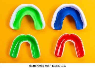 four colored mouthguards on a yellow background, two adults and two children's mouthguards, tooth protection, the concept