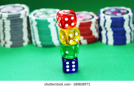Four colored translucent dice with white numbers, with some gambling chips in the background set against a green background.