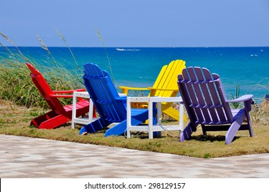 Four colorful Adirondack chairs invite visitors to enjoy a colorful ocean view overlooking this Florida beach.