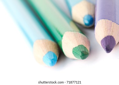 Four colorful crayons on white background with a shallow depth of field for effect.