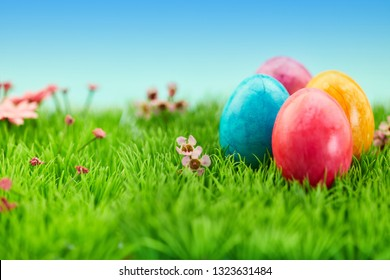 Four colorful Easter eggs for Easter in nature on a green meadow