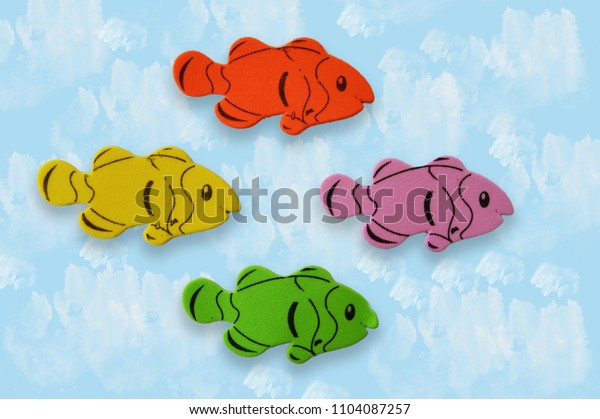 Four colorful of eva foam fishes isolated on a painted blue background