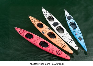 Four colorful fiberglass kayaks on a tether