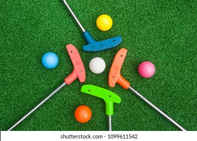 Four colorful golf putters with golf balls on synthetic grass