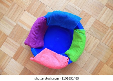 Four colorful microfiber cloths on blue plastic washbowl.It's time for cleaning.