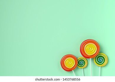 four colorful spiral lolipop on pastel color background.sweet candy concept