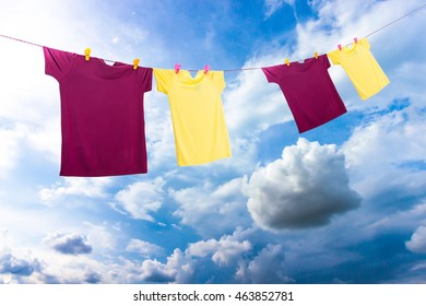Four a colorful summer t-shirt clothes  hanging on line for dry outdoor on sun and wind on blue sky background.