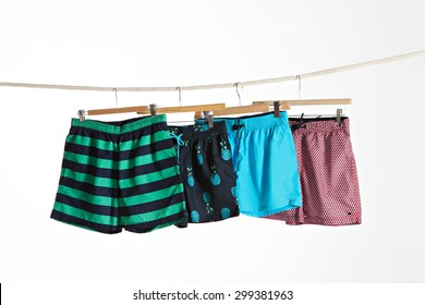 four colorful swimwear in a rope on a white background