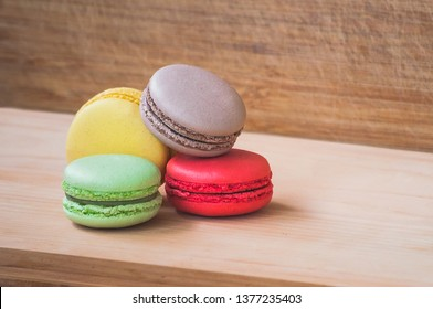 Four colorful tasty french macarons isolated on wood texture