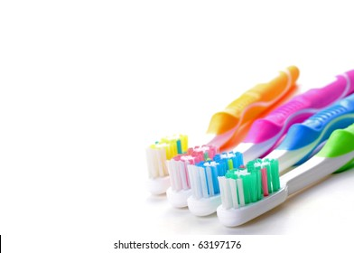 Four colorful toothbrushes on a white background.