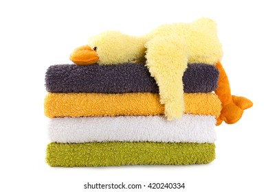 Four colorful towels with yellow plush duck isolated on white background