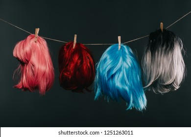 four colorful wigs hanging on rope isolated on black