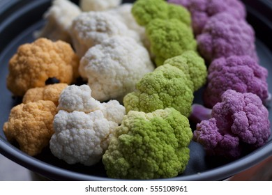 four colors of cauliflowers in a tray