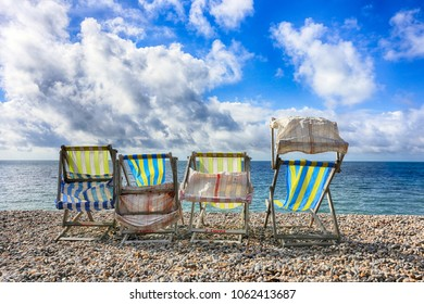 Four colourful deckchairs on a pebble beach on a windy day.