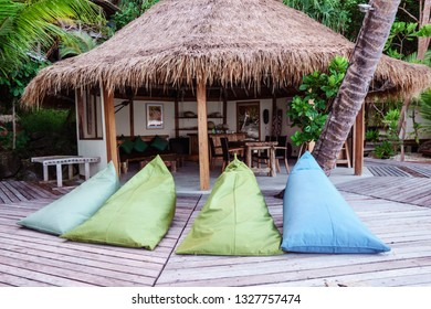 Four comfortable bean bags on a timber deck in front of a thatched wooden hut.