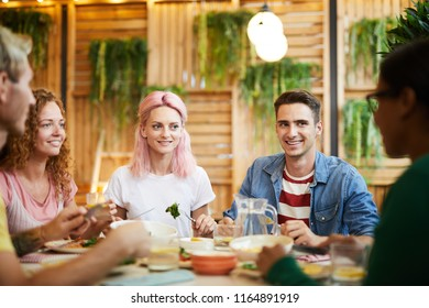 Four companions looking at their friend during conversation by festive dinner in cozy cafe