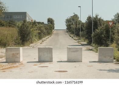 Four concrete blocks on the road (Pesaro, Italy, Europe)