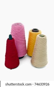 Four cones of wool on white background