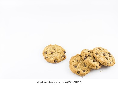 Four cookies with chocolate chips on a white background.