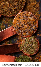 Four cooper spoons with cumin, basil, oregano and other spices lie on a dark background.