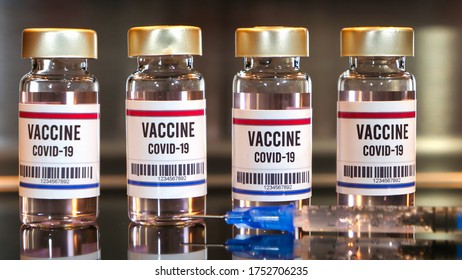 Four covid-19 vaccines and syringe on black table with reflections and stainless background.