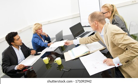 Four coworkers working frantically during a hectic project team meeting, finding solutions, and solving problems