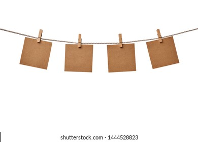 Four craft paper blank notes hanging on the rope with wooden clothespins isolated on white background